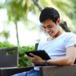 Ein junger Mann sitzt auf dem Sessel mit einem Tablet in der Hand